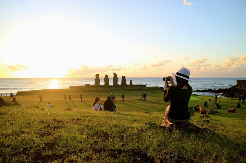 turystka na tle olbrzymow skalnych moai na wyspie wielkanocnej