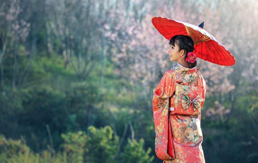 Japonka w tradycyjnym stroju na tle kwitnących wiśni.